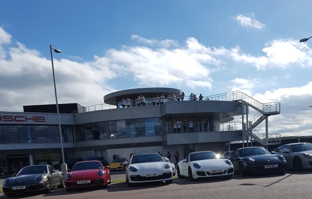 [Muscle Warrior team standing on a viewing platform looking down at a carpark filled with Porsche's]
