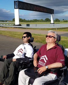 [2 men in wheelchairs wearing Muscle Warrior t-shirts looking across to Silverstone race-track]