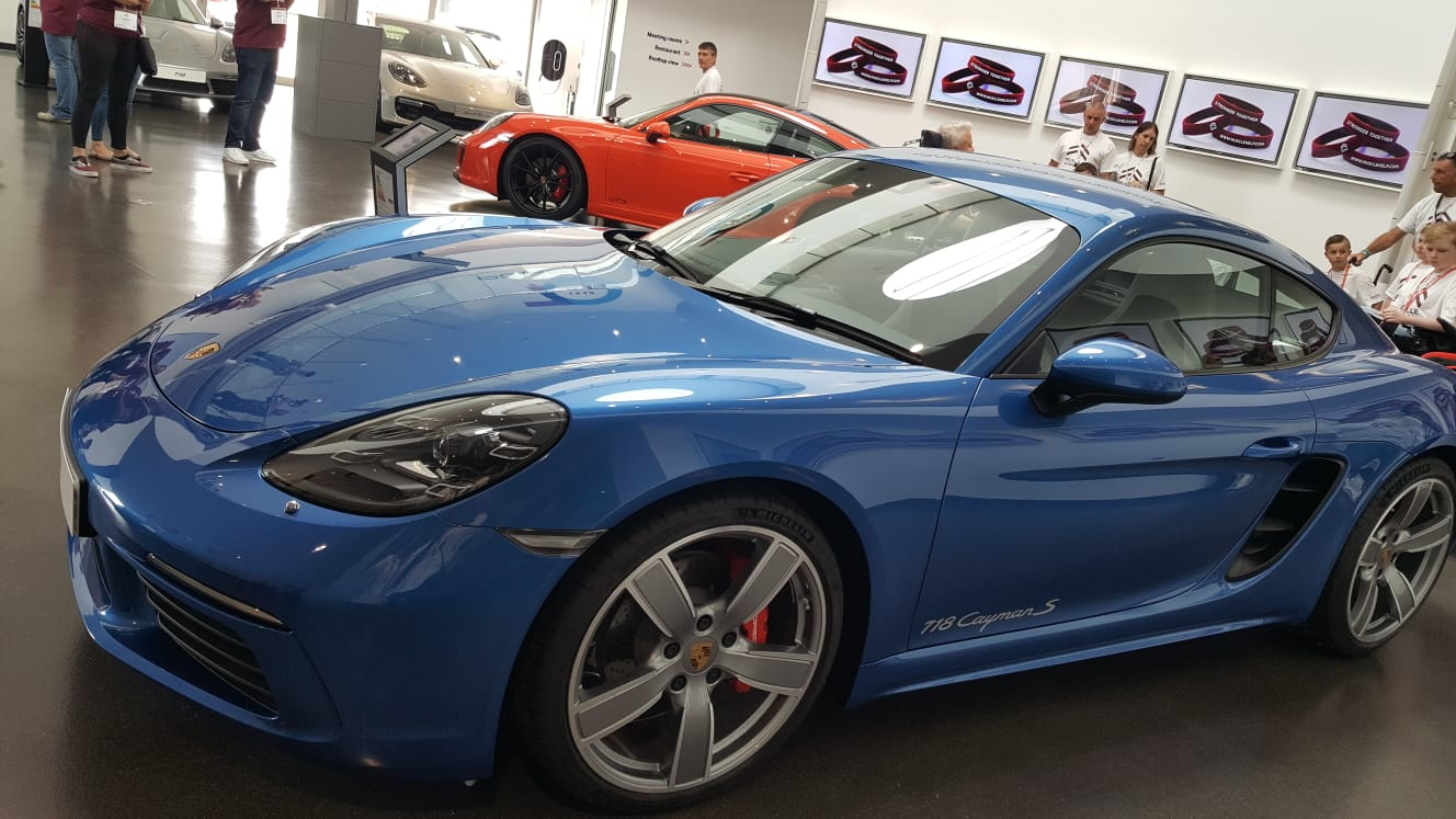 [Front and centre is a Blue Porsche 718 Cayman S, on the back wall monitors display Muscle Help Foundation's burgandy wristbands]