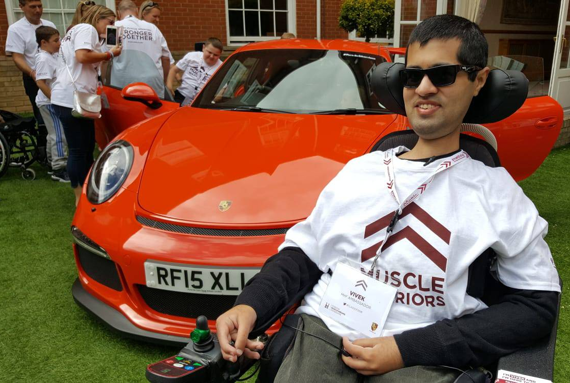 [Man in wheelchair smiling, wearing sunglasses and a Muscle Warrior t-shirt, sat in front of a red Porsche with its doors open]