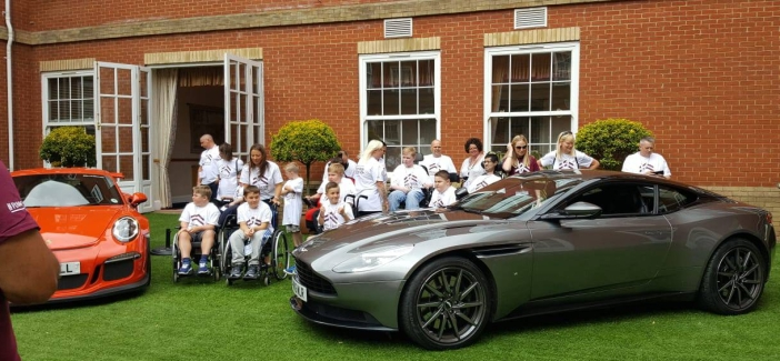 [Group of children in Muscle Warrior t-shirts sat between a Red Porsche and a Grey Aston Martin]